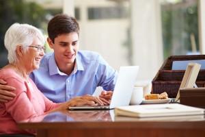 Teenage Grandson Helping Grandmother With Laptop