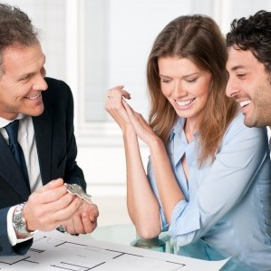 Happy estate agent showing new home keys to a young couple after a discussion on house plans.